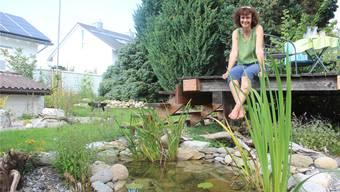 Christina Cotti in ihrem neuen, naturnahen Reich: In nur einem Jahr hat sie einen Teich und unzählige Versteckmöglichkeiten für Kleintiere geschaffen. Doch nicht nur die Tiere und Pflanzen, auch sie selbst kann sich in diesem Paradies sichtlich wohlfühlen.