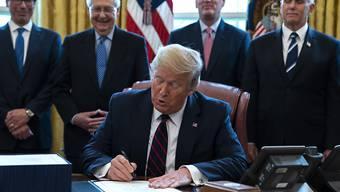 US-Präsident Donald Trump (Mitte) unterzeichnet im Oval Office des Weissen Hauses das Konjunkturpaket, mit dem rund 2 Billionen US-Dollar in die Wirtschaft gepumpt werden sollen.