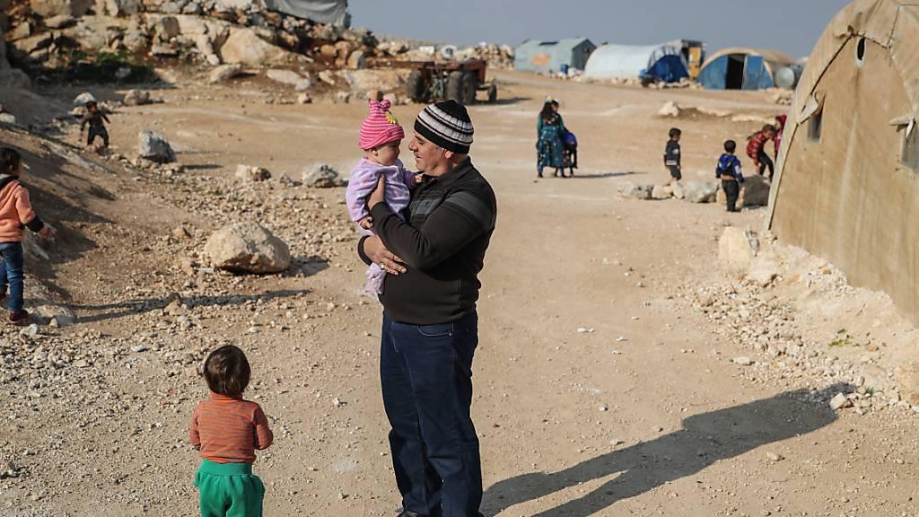 ARCHIV - Ein Mann steht mit seinen Kindern in dem Lager, in dem sie wohnen. Foto: Anas Alkahrboutli/dpa/dpa