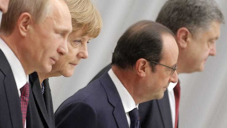 Steckten die Köpfe über den Ukraine-Konflikt zusammen: Putin, Merkel, Hollande und Poroschenko sprechen sich per Telefon ab. (Archivbild)