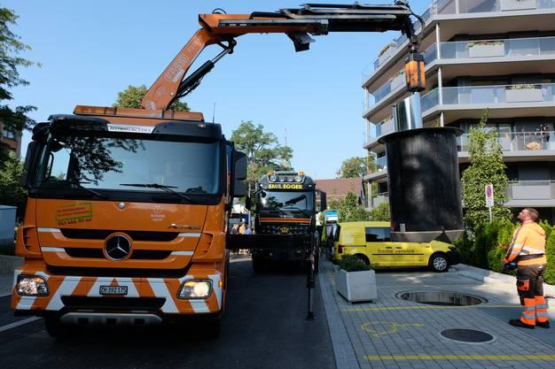 Doppeltes Spektakel: Bevor der Schwertransporter losfahren konnte, musste er aber noch schnell warten, bis der städtische Müllwagen den Unterflur-Müllcontainer geleert hatte.