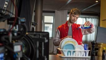 Bevor Mann das Geschirr in den Regen hinausstellt, kippt er eine Ladung Spülmittel dazu.