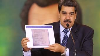 HANDOUT - Auf diesem vom venezolanischen Präsidentenamt zur Verfügung gestellten Bild zeigt Nicolas Maduro, Präsident von Venezuela, die Kopie eines Dokumentes, das beweisen soll, dass der Oppositionsführer Guaido einen angeblichen Invasionsversuch mit «terroristischen Söldnern» unterstützt haben soll. Die Regierung von Maduro versichert, «Söldner» hätten das Land angegriffen. Hinter dem Plan steckten Kolumbien und die USA. Das Präsidentenamt veröffentlichte ein Video, in dem ein festgenommener US-Bürger Details seiner Mitarbeit schildert. Foto: Marcelo Garcia/Prensa Miraflores/dpa - ACHTUNG: Nur zur redaktionellen Verwendung im Zusammenhang mit der aktuellen Berichterstattung und nur mit vollständiger Nennung des vorstehenden Credits