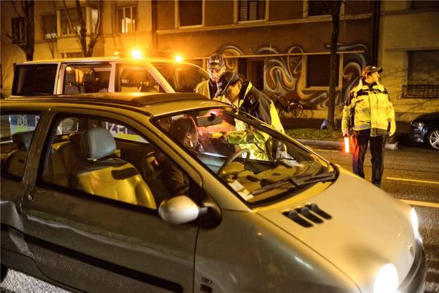 Ein Polizist hält das Testgerät hin, der andere behält sicherheitshalber die Situation im Auge.