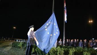 Eine kroatische Polizeioffizierin hisst die europäische Flagge in Bregana an der Grenze zwischen Kroatien und Slowenien