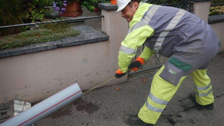 An einer Schnur werden ein Holzklotz und eine Bürste durch den Kabelkanal gezogen, um die Rohrweite zu überprüfen und den Kanal zu reinigen.