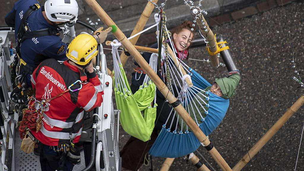 Klima-Aktivistinnen haben sich auf einem Holzgerüst angekettet - sie werden von Höhenrettern von Schutz & Rettung Zürich auf den Boden zurückgeholt.