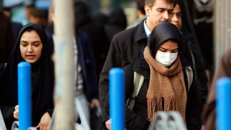 Eine Frau läuft mit einer Atemschutzmaske durch Irans Hauptstadt Teheran. Die Metropole gilt als eine der am stärksten verschmutzten Hauptstädte der Welt