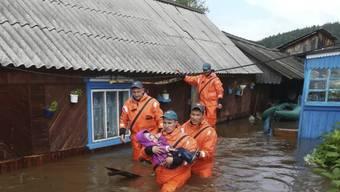 Helfer bringen ein Kind aus einem überfluteten Haus in Sicherheit.