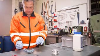 Ein Mitarbeiter des Basler Tiebauamts bindet die Köder für Ratten.
