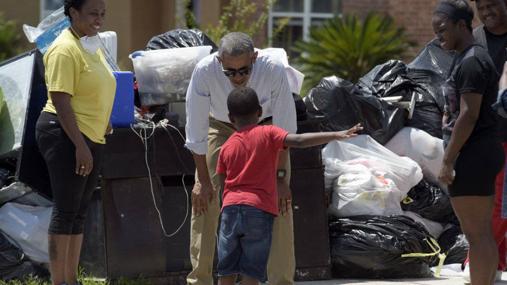 US-Präsident Barack Obama macht den Betroffenen der Überschwemmungen im US-Bundesstaat Louisiana Mut. Bei seinem Rundgang in Baton Rouge spricht er mit einem Knaben.