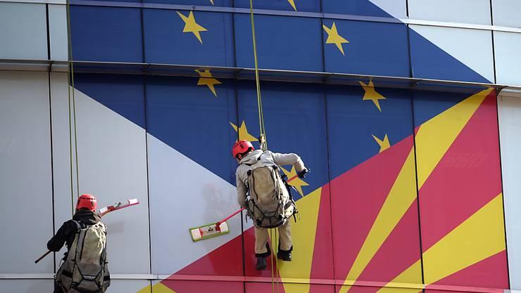 Arbeiter putzen die Fassade am EU-Büro in Skopje: Aufgemalt sind die Flaggen der EU und Nordmazedoniens.