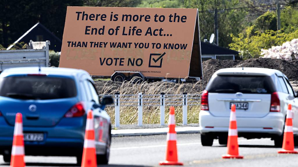 ARCHIV - Autos fahren auf einer Straße an einem Plakat vorbei, das Wähler dazu auffordert, mit «Nein» gegen Euthanasie zu stimmen. Die Bürger Neuseelands haben sich in einem Referendum jedoch für die Legalisierung der Sterbehilfe in dem Pazifikstaat ausgesprochen. Foto: Mark Baker/AP/dpa