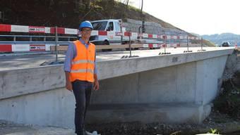 Projektleiter Martin Meier vor der neuen Brücke, im Hintergrund die Stützmauer.