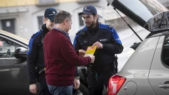 Mitarbeiter der Zollverwaltung verteilen an der Grenze zu Italien die neuen Informationsflyer des Bundes.