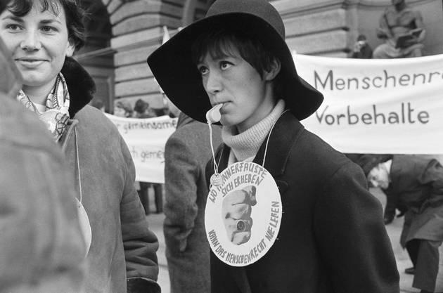 Frauen machen mit Trillerpfeifen auf ihre Anliegen aufmerksam. Eine Frau, die Trillerpfeife im Mund, trägt eine grosse Spruchplakette um den Hals mit der Aufschrift: «Wo Männerfäuste sich erheben, kann das Menschenrecht nie leben.»