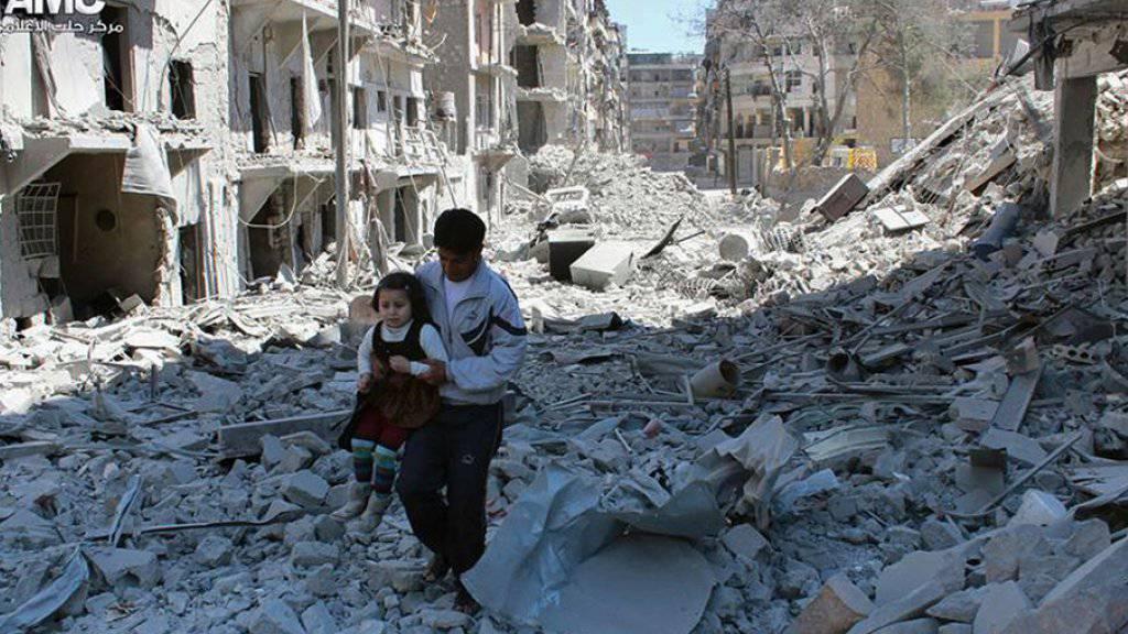 Mann mit Kind inmitten von zerstörten Häusern in Aleppo (Archiv).
