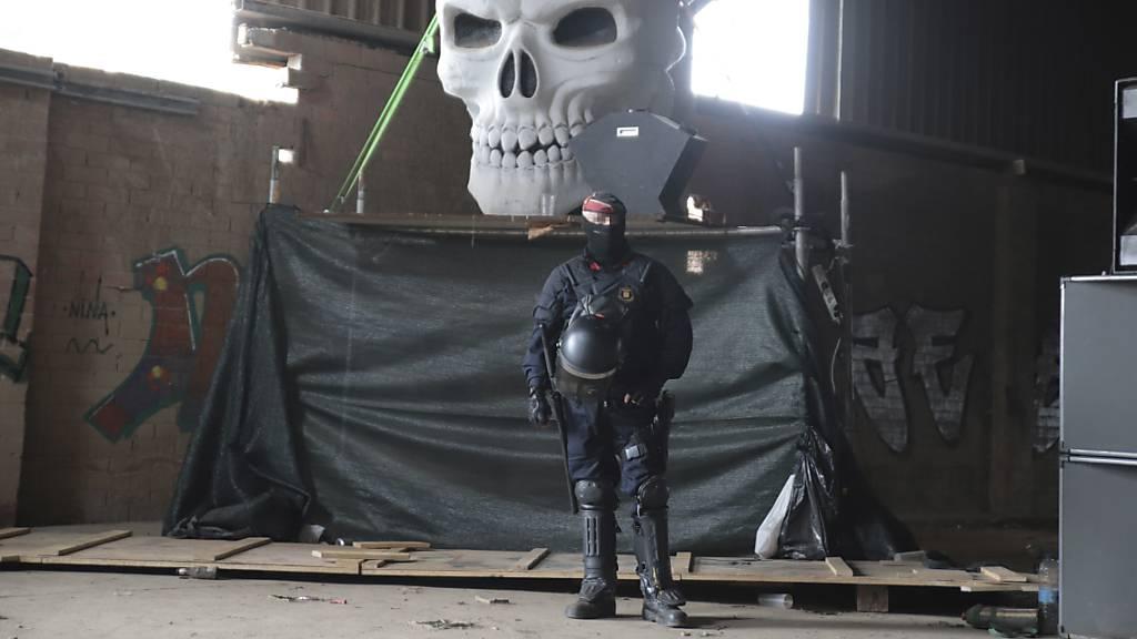Ein Polizeibeamter der Mossos d'Esquadra steht in einer Lagerhalle vor einem riesigen Totenkopf, während vor Ort ein Rave aufgelöst wird.