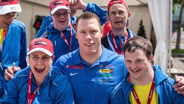 Auch so macht sich die Organisation bekannt: Schwingerkoenig Matthias Sempach mit Athleten von Procap Zug anlässlich der National Summer Games Bern 2014 im Mai.