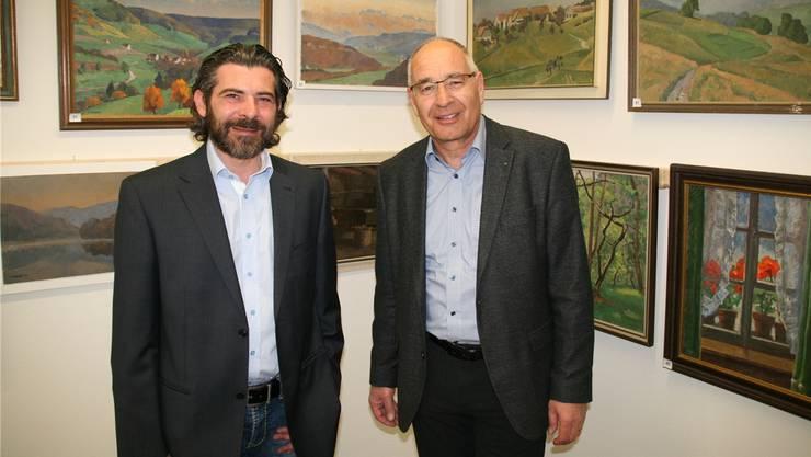 Armando Filippi (links) und Gemeindepräsident Peter Weber stehen vor Bildern von Ernst Wülser. psc