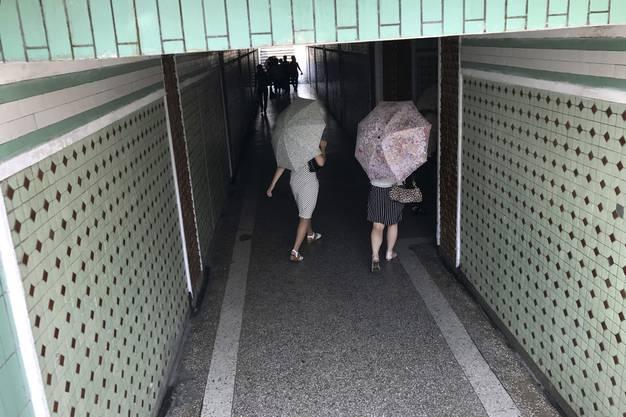 Diese Frauen schützen sich mit Schirmen gegen die Sonneneinstrahlung.