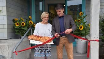 Bibliotheksleiterin Heidi Hasler und Gemeindeammann Ueli Lütolf durchschneiden das Band an der Neueröffnung.