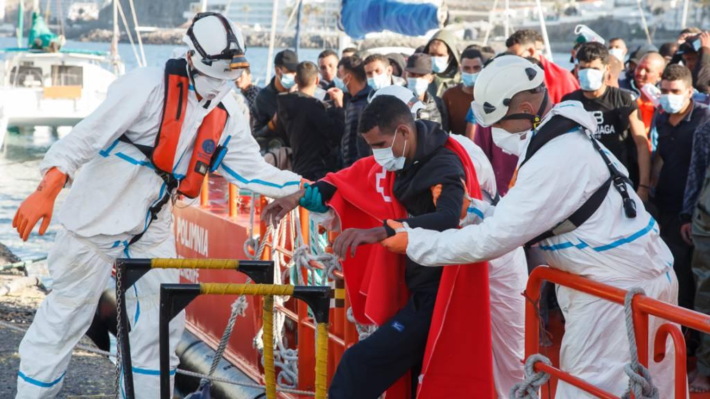 Mitarbeiter des Roten Kreuzes in Schutzkleidung helfen bei der Überführung von Migranten aufs Festland. Auf den Kanarischen Inseln vor der Westküste Afrikas sind am Freitag (09.10.20) mehr als 700 Migranten in 22 Booten angekommen. Das war die höchste Tageszahl seit der Migrationskrise 2006. Foto: Europa Press/EUROPA PRESS/dpa