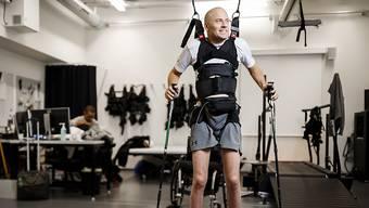 Der Schweizer Paraplegiker Sebastian Tobler kann dank Elektrostimulation, Training und mit Stützen wieder eigene Schritte tun.