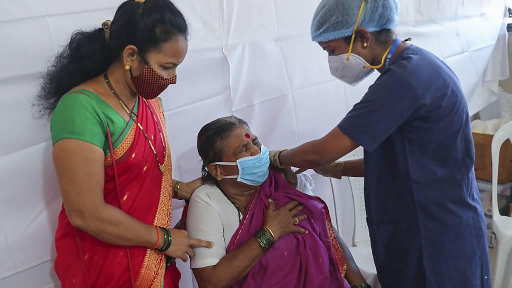 Eine Frau erhält von einer medizinischen Mitarbeiterin eine Corona-Schutzimpfung mit dem AstraZeneca-Impfstoff, der in Indien unter dem Namen Covishield vertrieben wird. Foto: Rafiq Maqbool/AP/dpa