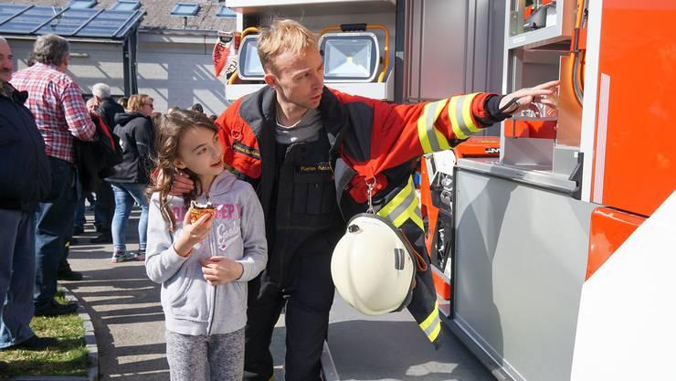 Feuerwehrmann Florian Ruhland erklärt seiner Cousine Aleyna das neue Feuerwehrauto.