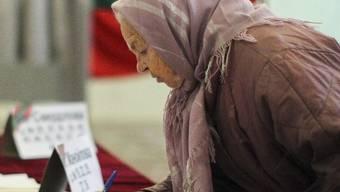 Eine ältere Frau gibt in Tiraspol in Moldawien ihre Stimme ab