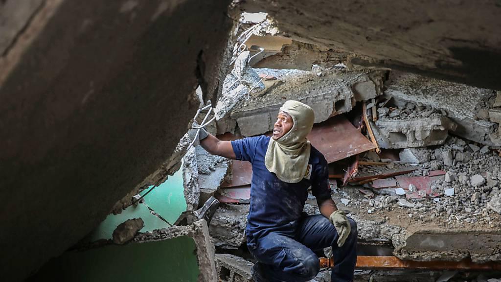dpatopbilder - Ein Feuerwehrmann sucht zwischen den Trümmern eines von einem Erdbeben zerstörten Hauses nach Überlebenden. Das Erdbeben der Stärke 7,2 hat Haiti am 14.08.2021 erschüttert. Foto: Joseph Odelyn/AP/dpa