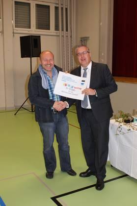 Mani Haller (rechts) überreicht Andreas Albiez den Gutschein für einen Kulturanlass