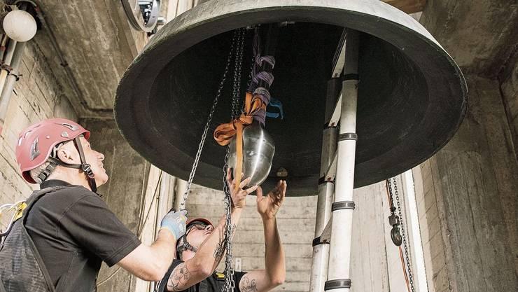 Arbeiten in 35 Meter Höhe: Frank Hofer (l.) und Tom Zingrich hieven den neuen, 80 Kilo schweren Klöppel in die Kirchenglocke.
