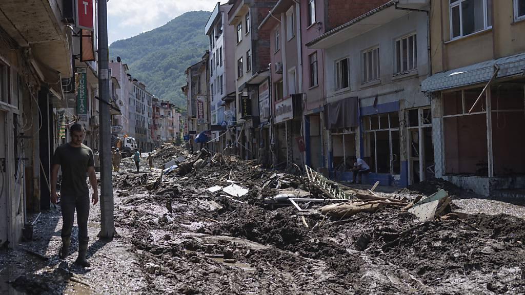 Ein Mann geht durch eine Straße, die voller Schlamm und Schutt ist. In der türkischen Schwarzmeerregion führten heftige Regenfälle in den vergangenen Tagen zu den schlimmsten Überflutungen seit Jahren. Foto: -/AP/dpa
