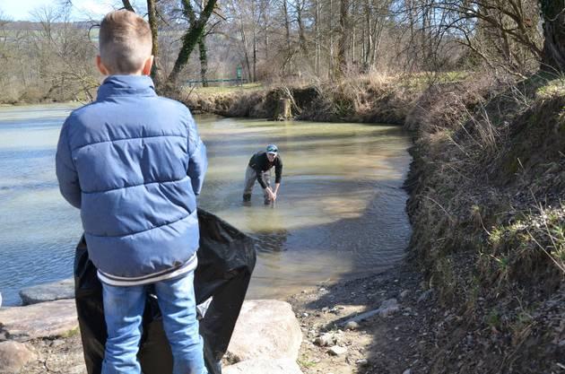Nicola Meier zieht ein Metallrohr aus dem Uferbereich der Reuss beim Dammspitz. Jungfischer Colin Klauser wartet schon mit dem Abfallsack auf ihn.