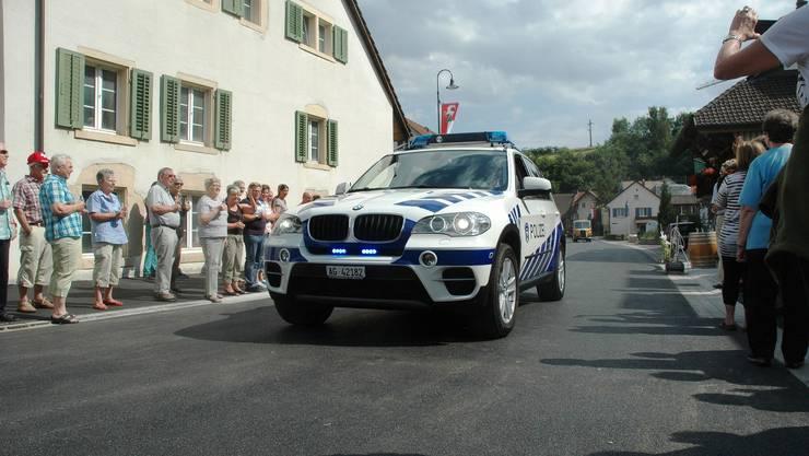 Als erstes fährt das Polizeiauto über die sanierte Strasse