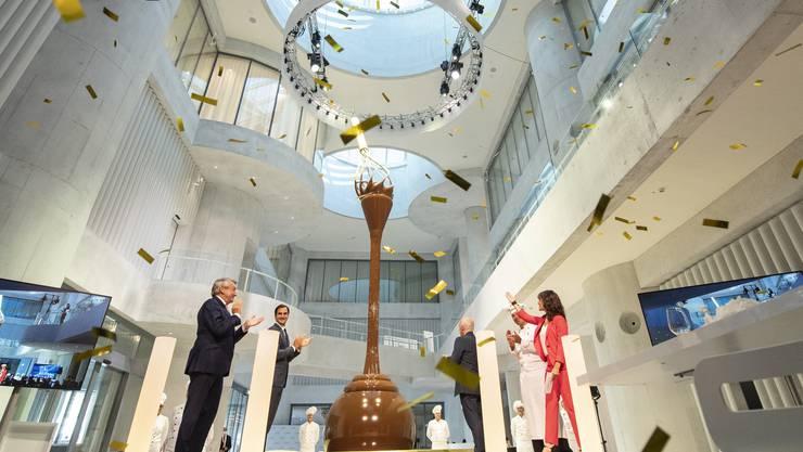 Bundesrat Ueli Maurer, Stiftungsratspräsident Ernst Tanner und Markenbotschafter Roger Federer enthüllen das Herzstück des neuen Lindt Home of Chocolate – den über neun Meter hohen Schokoladenbrunnen.