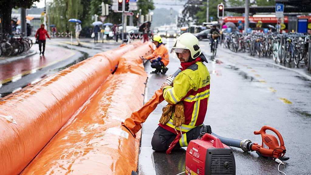 Die Feuerwehr schützt in Luzern die Bahnhofstrasse mit wassergefüllten Schläuchen vor Überschwemmungen.