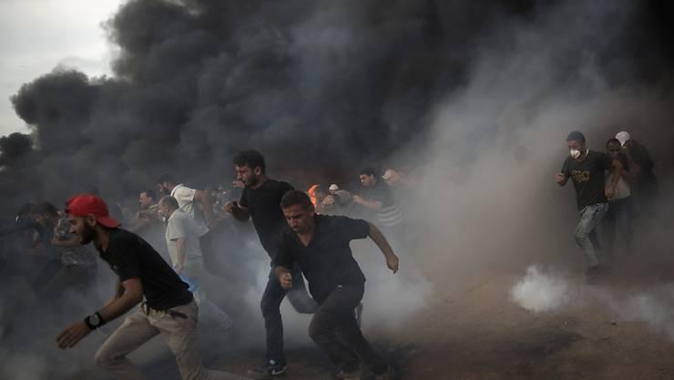 Protestierende Palästinenser fliehen vor den Tränengaswolken, die Israels Streitkräfte an der Grenze zum Gazastreifen einsetzten.
