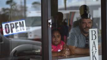 Skeptische Blicke auf die Verwüstung: Ein Mann und ein Mädchen schauen aus einer Bäckerei in Freeport auf den Bahamas.
