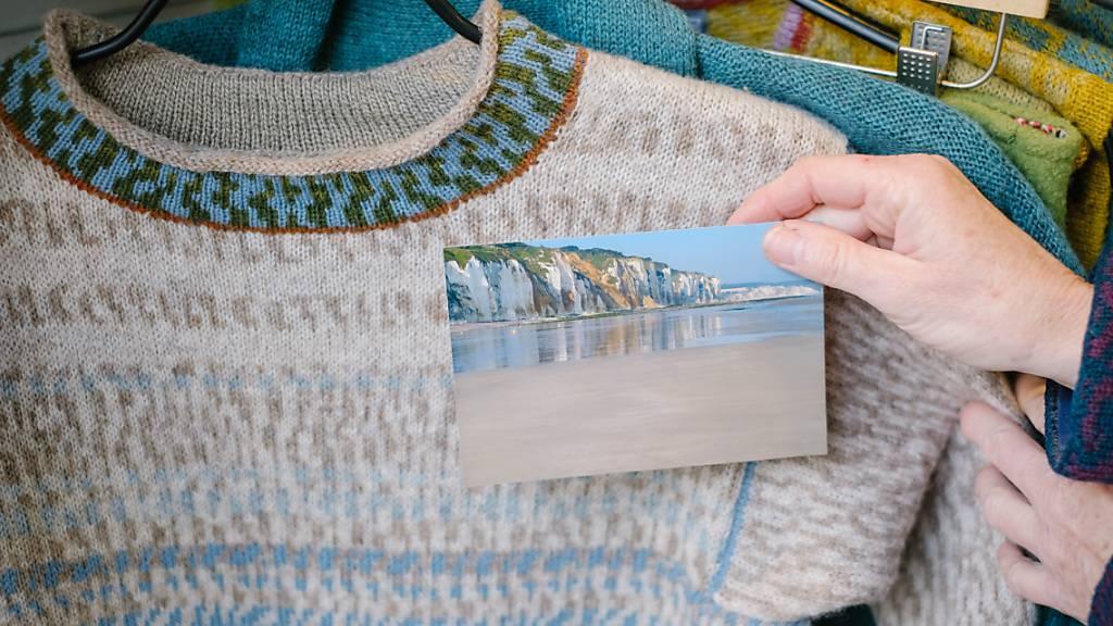 Die Textildesignerin Anne-Susanne Gueler hält in ihrem Werkstattladen «hand-werk» ein Foto aus der Normandie neben einen von ihr gestrickten Pullover. Gueler lässt sich häufig von Landschaften inspirieren. Foto: Ole Spata/dpa