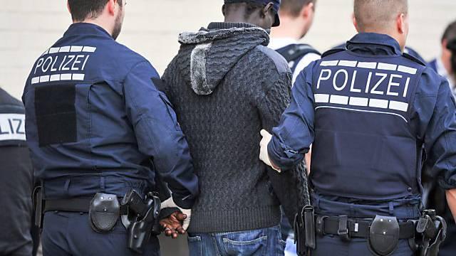 Deutsche Polizisten führen einen Flüchtling ab (Symbolbild)