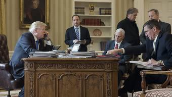 US-Präsident Donald Trump (l) im Telefongespräch mit Russlands Präsident Wladimir Putin. Mit im Oval Office unter anderem Vize-Präsident Mike Pence (Mitte sitzend) und Sicherheitsberater Michael Flynn (r)