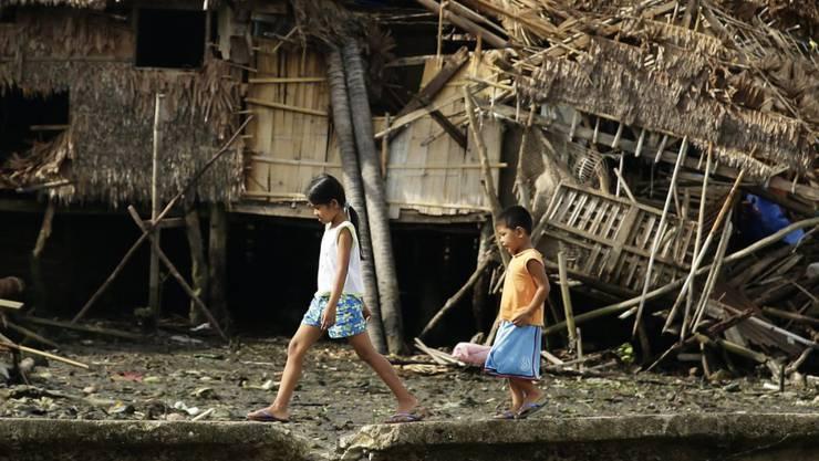 """Kinder gehen über einen Deich, vor vom Taifun """"Melor"""" zerstörten Häusern."""
