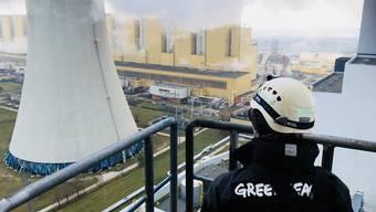 Ein Greenpeace-Mitglied schaut am Dienstag hinüber zum Schornstein des Kohlekraftwerks im südpolnischen Belchatow, den neun Aktivisten erklommen.