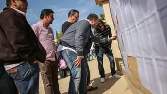 Wähler schauen sich in Bengasi ein Wahlregister an