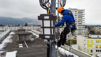 Ein Techniker installiert im April dieses Jahres auf einem Genfer Gebäude eine 5G-Antenne. (Archivbild)