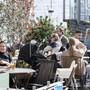 Die Menschen geniessen das frühlingshafte Wetter in einem Restaurant in Stockholm.