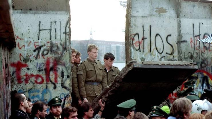 Nach 28 Jahren der Trennung begannen die Berliner nach der Grenzöffnung am 9. November 1989, die Mauer zu demontieren. Ehemalige DDR-Grenzsoldaten schauen ihnen belustigt zu.
